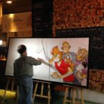 Frank Pé painting in a Paris café (photo (c) Dupuis, from facebook.com)