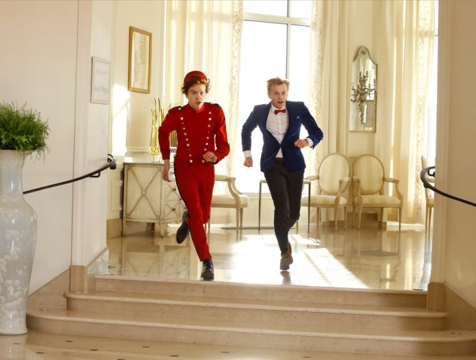 Spirou and Fantasio (Thomas Solivérès and Alex Lutz) running in hotel, from film shoot (image from facebook.com/SpirouEtFantasio.Film/)